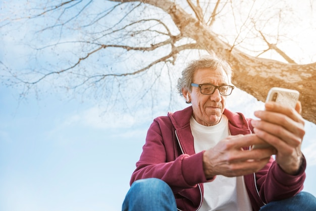 上の男は、彼の耳にbluetoothイヤホンと携帯電話を使用してツリーの下に座って