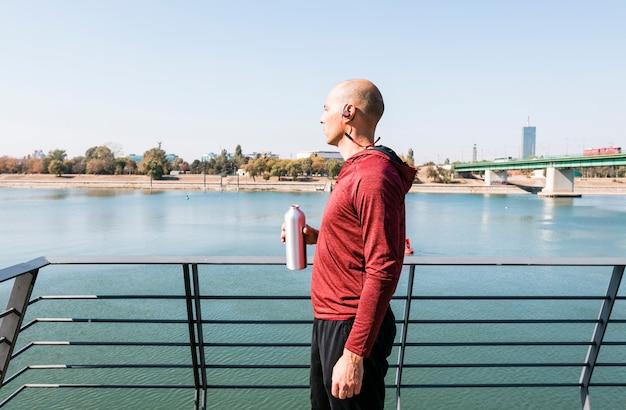 ビューを見て手に水のボトルを保持している彼の耳にワイヤレスのbluetoothを着ているオスの運動選手