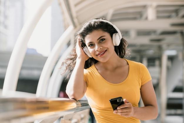 音楽を聴くbluetoothヘッドフォンを着ている女性