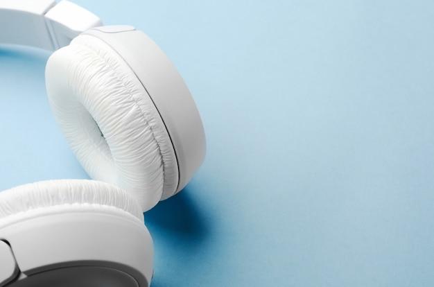 青色の背景に白いオーバーヘッドワイヤレスbluetoothヘッドフォン。クローズアップ、コピースペース。