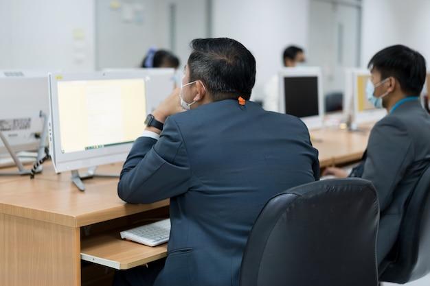 Размытие и выборочный фокус взрослых студентов университетов в маске, сосредоточенных на выполнении онлайн-экзамена в компьютерном классе. серьезные студенты, работающие на компьютере в университете