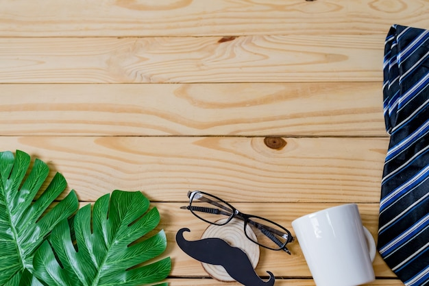 Blur of background, happy father's day concept. a black mustache paper, a blue necktie, a blue gift box and glasses on wooden table.