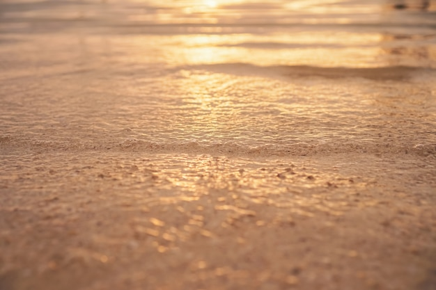 Blur beach with bokeh orange sunset theme color.
