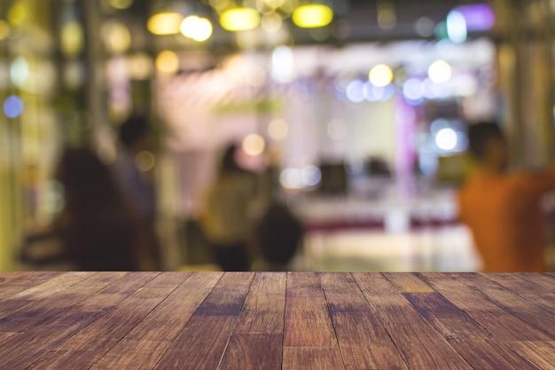Запачкайте ресторан или кофейню кафа пустые темного деревянного стола с запачканной светлой предпосылкой конспекта bokeh золота.