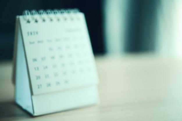 Размытие страницы календаря крупным планом на фоне деревянного стола.