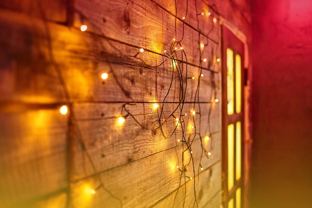 Blur christmas lights on wooden planks and door. bright glowing garland. new year lights background