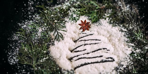 松の枝の丸いフレームの黒い背景に小麦粉のクリスマスツリーをぼかす