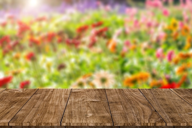 Blur colorful flower field with wooden table top blank space for natural aroma or perfume products advertising montage template.