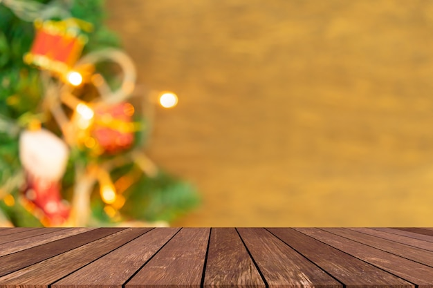 Blur decorated christmas ornament pine tree in home interior background with old wood tabletop for design