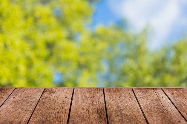 製品のプレゼンテーションのための木製のテーブルの前景と緑の木の背景をぼかす