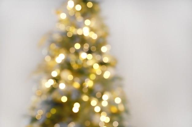 白い壁の背景とクリスマスツリーの光のお祝いをぼかします。休日の背景の焦点をぼかす。