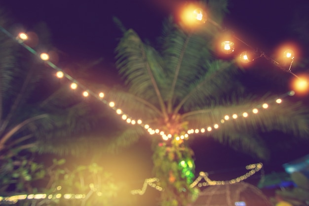 Blur light with coconut palm tree, yellow string lights with bokeh decor in outdoor restau