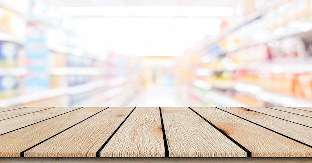 Blur local supermarket convenience store background with beige wood perspective tabletop