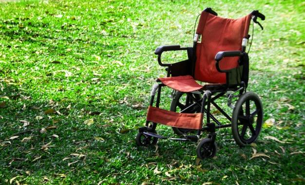 ぼやけた人は緑の草の上に車椅子を立てた