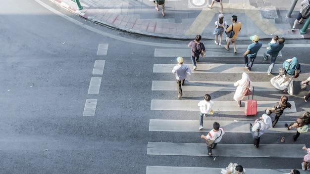 Размытые люди перемещаются по пешеходной дорожке на городской дороге