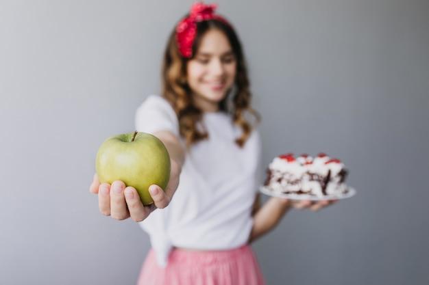 Размытие фото смеющейся женской модели с зеленым яблоком на переднем плане. крытый портрет возбужденной девушки, позирующей с тортом