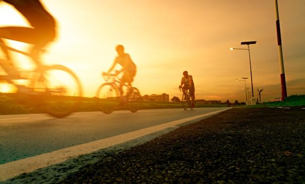 흐릿한 사진 스포츠 남자는 일몰 하늘과 함께 저녁에 도로에서 속도 동작으로 자전거를 탄다. 건강하고 행복한 삶을 위한 여름 야외 운동. 자전거 차선에서 산악 자전거를 타는 자전거. 팀.