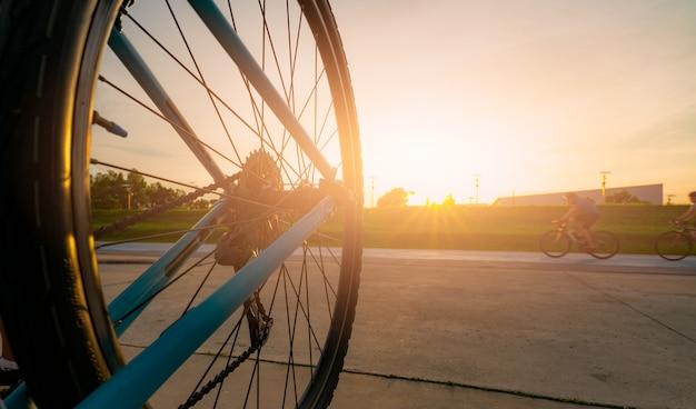 흐릿한 사진 스포츠 남자는 일몰 하늘과 함께 저녁에 도로에서 속도 동작으로 자전거를 탄다