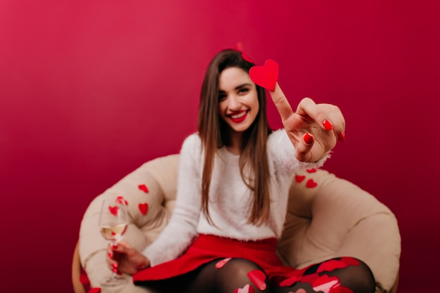 Blur portrait of long-haired girl with her hand holding heart in focus