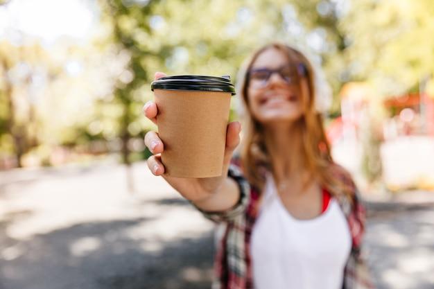 一杯のコーヒーを保持している愛らしい女性のぼやけた肖像画。夏の日を楽しんでいるのんきなスタイリッシュな女の子。