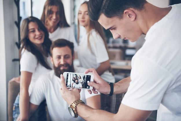 Размытие портрет блаженных молодых лучших друзей с руки, держа телефон на переднем плане