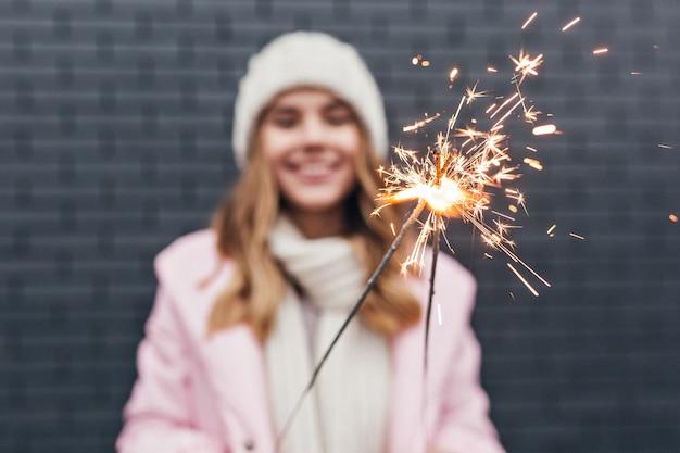 Sfocatura ritratto di sensuale ragazza in abiti invernali per celebrare il nuovo anno. foto all'aperto di donna allegra in cappello con sparkler in primo piano.