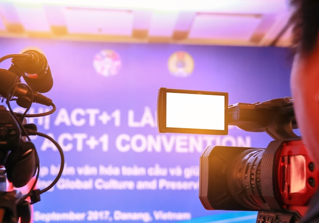 Blur of video camera or camcorder operator working his camera equipment for record in conference and convention hall.