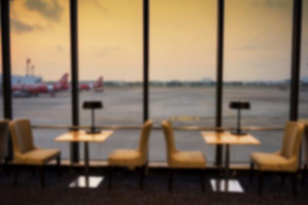 아침 해가 뜨면 비행기와 활주로 배경이 있는 공항 터미널 창 옆의 대기 좌석을 흐리게 합니다. 여행 휴가 휴가를 위해 출발을 기다립니다.