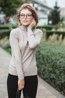 Blur young blonde student with blue eyes in a beige sweater and stylish glasses looks holding a black women's handbag
