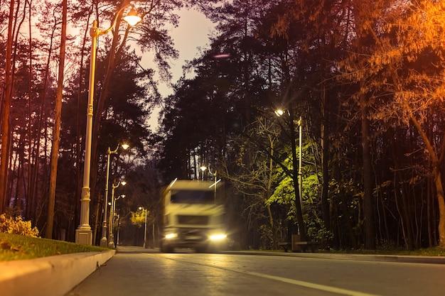 Размытый грузовик едет по ночному городскому парку