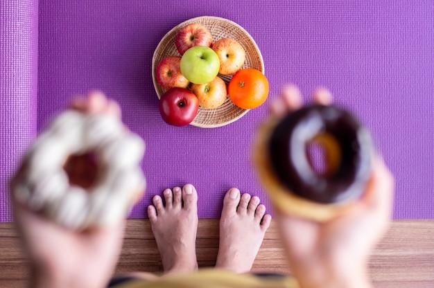 요가 매트에 신선한 과일과 함께 구운 도넛을 들고 있는 흐릿한 여성의 손, 건강한 식단, 다이어트 개념, 탑 뷰