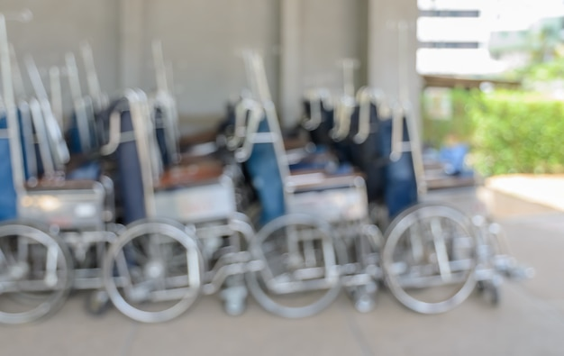 Blurred abstract background of manual or self-propelled wheelchairs in the hall of hospital