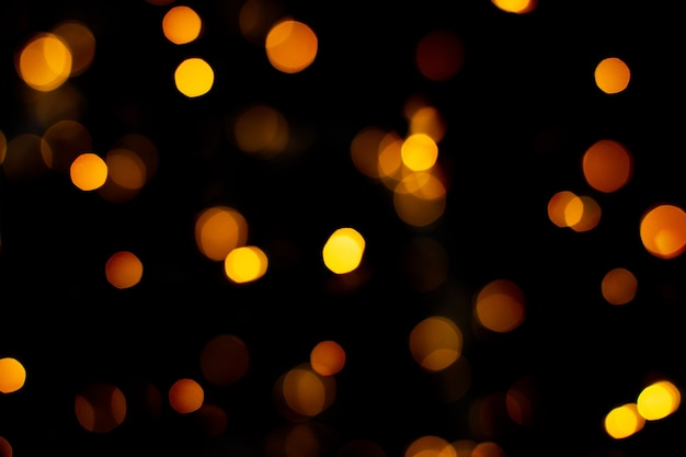Blurred abstract gold glitter texture, defocused christmas lights on black