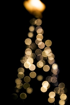 Blurred abstract golden sparkling lights on christmas tree background on black backdrop