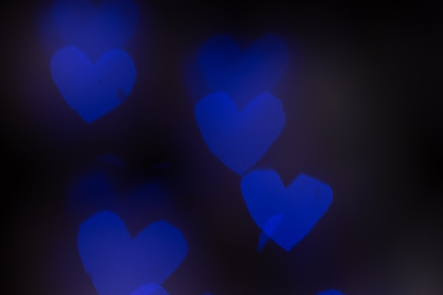 Blurred abstract hearts selective focus dark background. valentines day concept