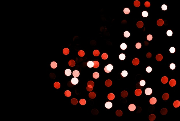 Blurred abstract sparkling lights background with heart shape on black backdrop.