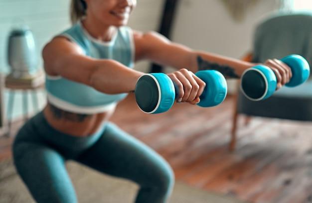 レギンスと自宅でダンベルを持ったトップのしゃがみで美しい若い運動少女のぼやけてトリミングされた画像。スポーツ、健康的なライフスタイル。