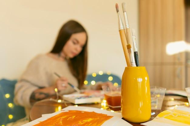 彼女の絵に取り組んでいるぼやけたアーティスト