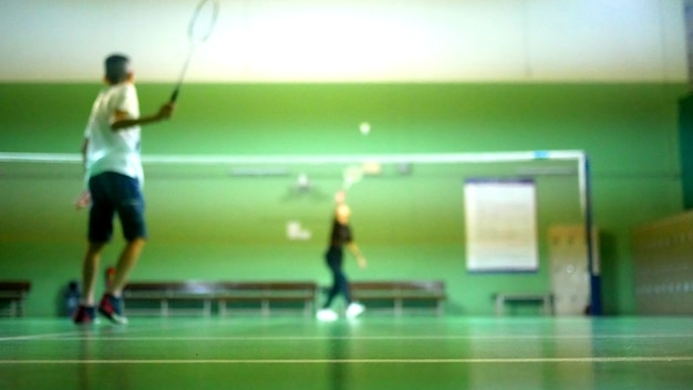 Blurred of back view of boy playing badminton with friend in badminton court.