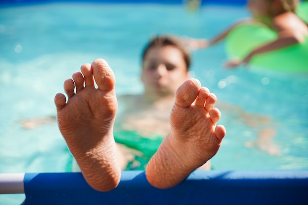 Blurred background closeup of the feet of children relaxing in the pool in the summer in the backyar...