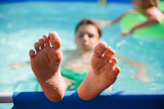 Размытый фон крупным планом ног детей, отдыхающих в бассейне летом на заднем дворе ...