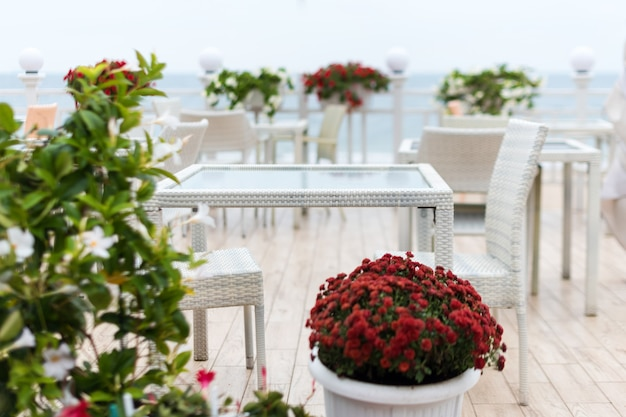 Blurred background,empty tables and chairs of a restaurant on a terrace overlooking the sea.