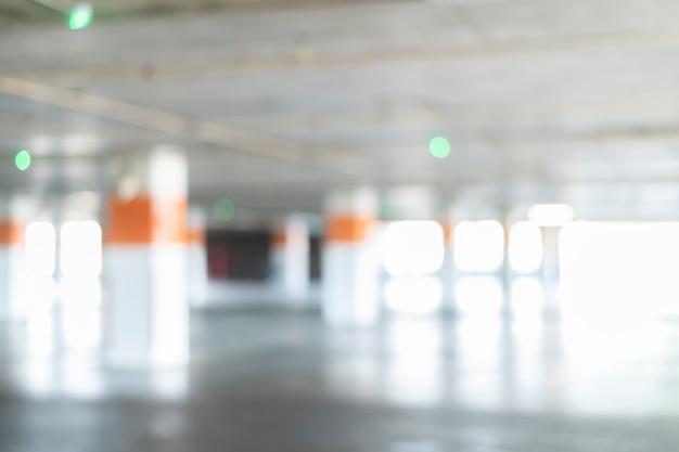 Blurred background of empty underground car parking garage