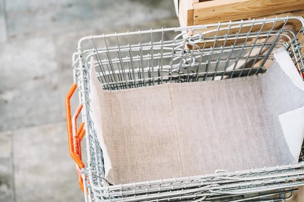 식료품 쇼핑을 위한 빈 금속 바구니가 있는 텍스트의 흐릿한 배경