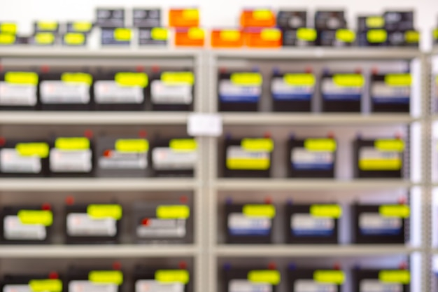 Blurred background in the form of a rack with car batteries in a store.