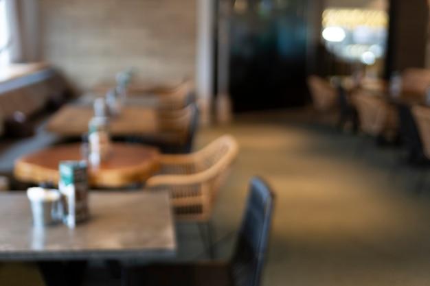 Размытый фон из абстрактного кафе с деревянными столами и золотыми огнями на заднем плане