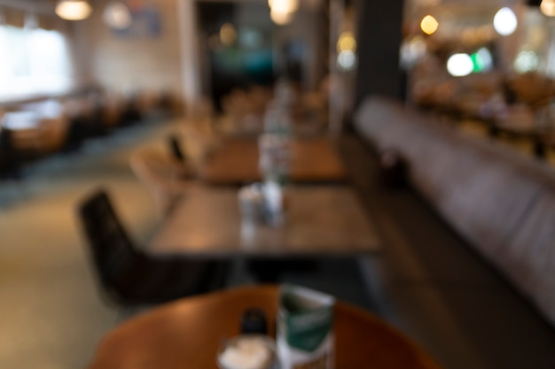 Blurred background from abstract cafe with wooden tables and golden lights in the background