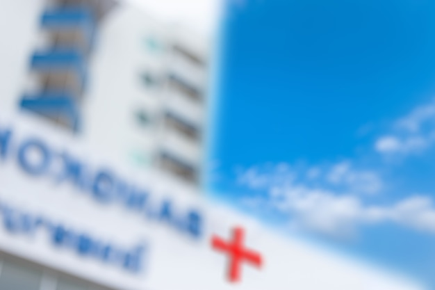 Blurred background of hospital building with red cross sign