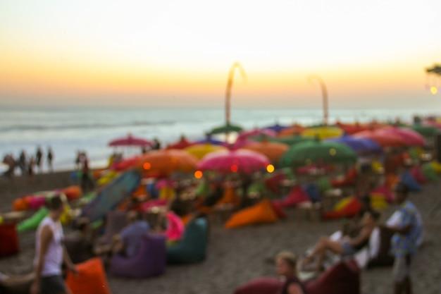 На размытом фоне многие люди веселились на пляжной вечеринке. праздничная концепция.