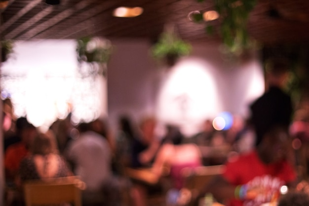 На размытом фоне многие люди веселились в пляжном ресторане. праздничная концепция.